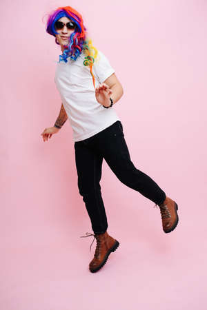 Photo pour Feminine man playing girl, jumping around and playing cute. He is wearing rainbow colored wig and sunglasses. Over pink background - image libre de droit
