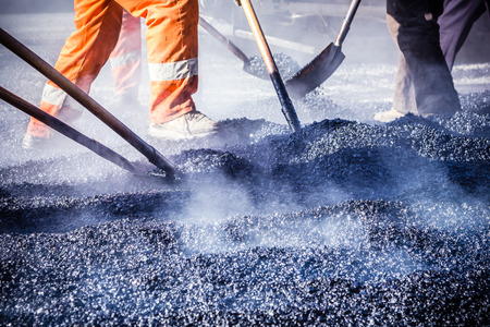 Photo for Workers making asphalt with shovels at road constructio - Royalty Free Image