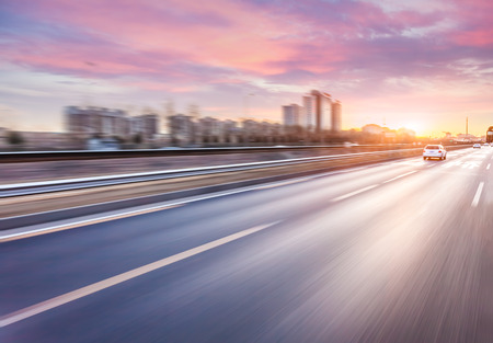 Photo for Car driving on freeway at sunset, motion blur - Royalty Free Image