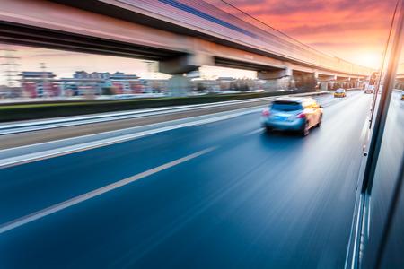 Photo pour Car driving on freeway at sunset, motion blur - image libre de droit