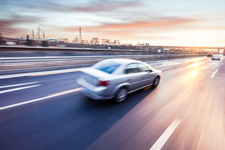Photo pour Car driving on freeway at sunset, motion blur - image libre de droit