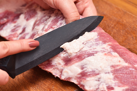 Photo pour Trim excess fat from pork meat on the ribs. To remove unwanted fat on the meat. - image libre de droit