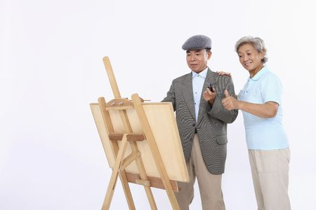 Photo for Senior woman complimenting senior man's art work - Royalty Free Image