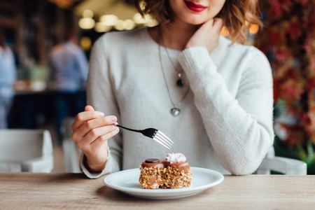 Photo for Closeup of woman eating chocolate cake in a cafe - Royalty Free Image