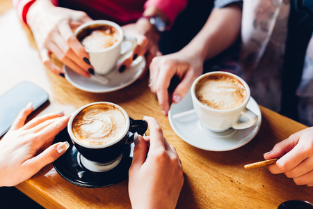 Photo for Closeup of hands with coffee cups in a cafe - Royalty Free Image