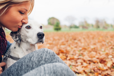 Closeup of happy owner woman kissing dog in autumn park with empty space