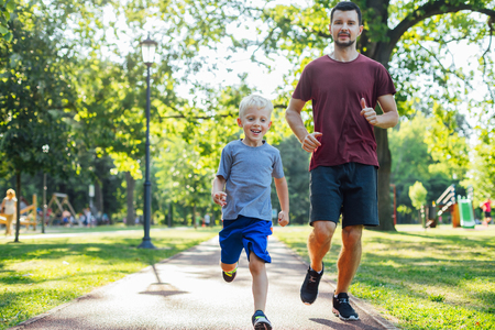 Foto de Father and son running together in the park - Imagen libre de derechos