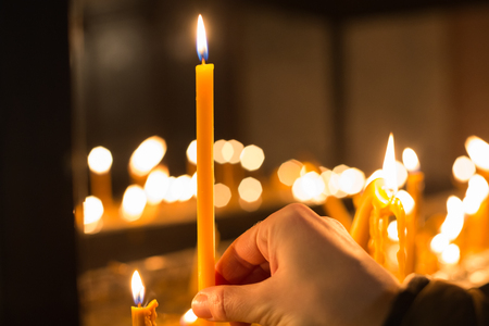 Photo for Hand holding candle in front of defocused candle flames - Royalty Free Image