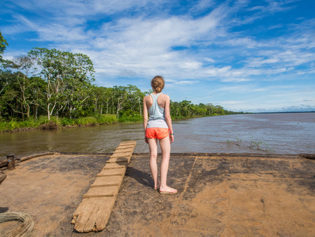 Photo for Amazon River, Peru - May 12, 2016: Young woman looking for  the Amazon River from the deck of cargo boat - Royalty Free Image