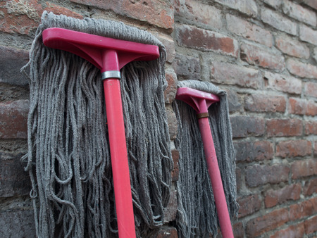 Foto de Floor cleaning brushes leaning against a brick wall - Imagen libre de derechos
