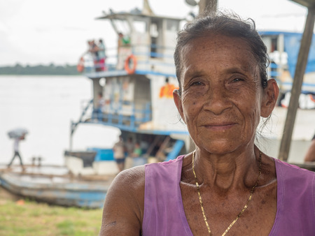 Photo for Caballococha, Peru- Dec 11, 2017:  Portrait of a woman with a red skin on the background of cargo boat in the Amazon  jungle - Royalty Free Image