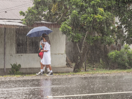 Foto de Ambon, Indonesia - February 12, 2018: Children in the white uniforms coming back from the school in the heavy rain - Imagen libre de derechos