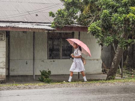 Foto de Ambon, Indonesia - February 12, 2018: Children in the white uniforms coming back from the school in the heavy rain - Imagen libre de derechos