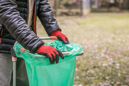 Foto de The hands of a mature man in working gloves fasten a green sack on the rack during the springtime gardening - Imagen libre de derechos