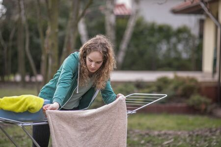 Foto de A young woman hangs the laundry in the garden - Imagen libre de derechos
