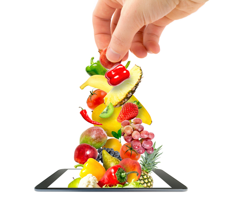 Photo pour A man's hand putting a pile of fresh vegetables and fruits flying into a modern gadget, a mobile phone, isolated on a white background. Online Shopping idea. - image libre de droit