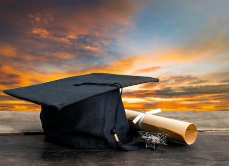 Photo for graduation cap, hat with degree paper on wood table, sunset sky background Empty ready for your product display or montage. - Royalty Free Image