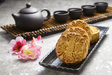 Photo for Golden Emerald mooncake on wooden table. Chinese mid autumn festival foods - Royalty Free Image
