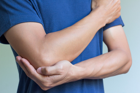 Foto de male having pain in injured arm - Imagen libre de derechos