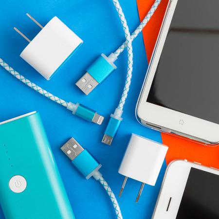 Foto de USB charging cables for smartphone and tablet in top view on blue and orange background - Imagen libre de derechos