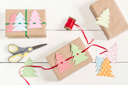 Photo pour Making gift boxes for Christmas with your own hands. DIY hobby. Boxes are wrapped in kraft paper, tied with ribbons with homemade colorful Christmas trees. Original gift decoration - image libre de droit
