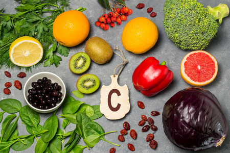 Photo pour Food is source of vitamin C.  Various natural food rich in vitamins. Useful food for health and balanced diet. Prevention of avitaminosis. Small cutting board with name of vitamin C. Top view - image libre de droit