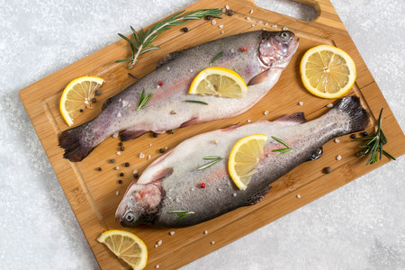 Foto de Two fresh trout on cutting board and ingredients for cooking (pepper, salt, lemon, seasoning and rosemary). Dietary and healthy food - Imagen libre de derechos