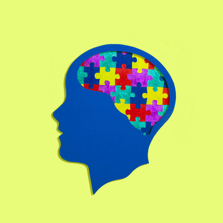 Foto de Stylized head silhouette. Multi-colored puzzles instead of brain. Symbol of autism, problems with social interaction and communication. Concept of mental health and disease - Imagen libre de derechos