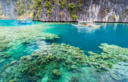 Photo for View of Kayangan Lake lagoon with tourists boat and coral reef on Coron island, Busuanga Palawan Philippines - Royalty Free Image