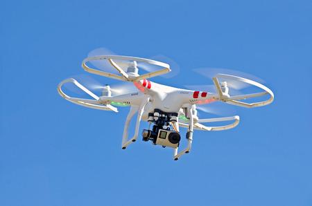 Foto de white drone hovering in bright blue sky - Imagen libre de derechos