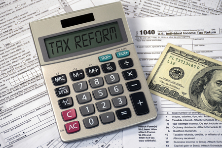 Photo pour Tax reform text on calculator screen with hundred dollar bill on income tax form - image libre de droit