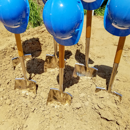 Photo for industrial blue hard hats on shovels in dirt for ground breaking ceremony - Royalty Free Image