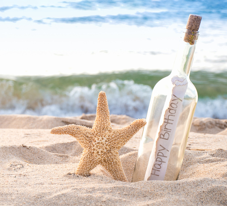 Photo pour close up of starfish and happy birthday message in a bottle on the seashore with water background - image libre de droit
