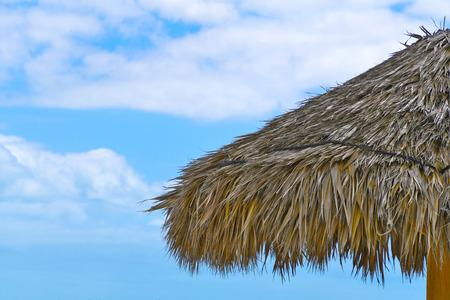 Photo pour tropical thatched grass tiki hut roof with blue sky and clouds - image libre de droit