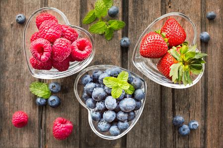 Foto de Mix of fresh berries in three  glass ramekins in shape of heart, on wooden background, top view, horizontal composition - Imagen libre de derechos