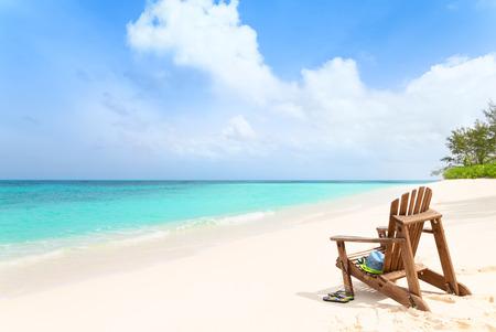 Foto de Wooden beach chair with hat, sunglasses and slippers at tropical beach, summer holiday concept - Imagen libre de derechos
