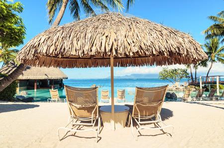 Photo pour Two Sun-loungers and Tiki hut sun umbrella on tropical beach - image libre de droit