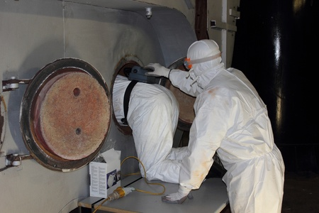 engineer s wearing ppe for an industrial boiler clean inside the furnance