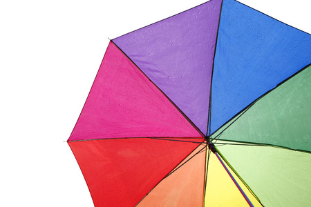 Colorful umbrella with rain drops in cloudy sky