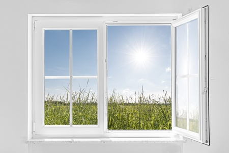 Photo pour picture of a white wall with white half open window indoor and outside green meadow with sun and blue sky - image libre de droit