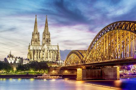 Foto de Illuminated Dom in Cologne with bridge and rhine at sunset - Imagen libre de derechos