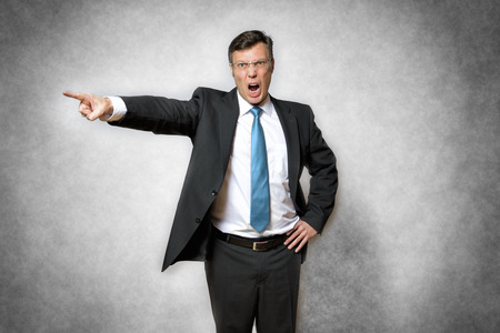 Photo pour image of angry business man in suit who is screaming and pointing with finger - image libre de droit