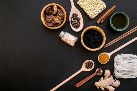 Photo pour Chinese and Japanese food cooking with ginger, spices and noodles on black background top view mock-up - image libre de droit