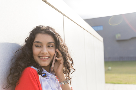Photo for Woman calling on phone standing next to a  wall wearing red jacket - Royalty Free Image