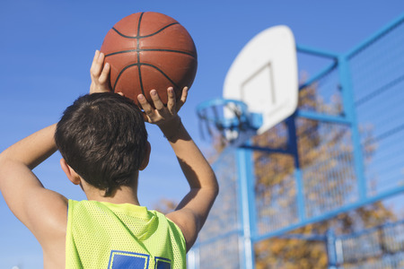 Photo for teenager throwing a basketball into the hoop from behind - Royalty Free Image