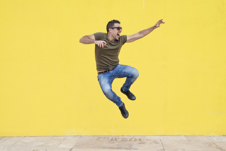 Foto de Young man with sunglasses jumping in front of a yellow wall ( freedom ) - Imagen libre de derechos