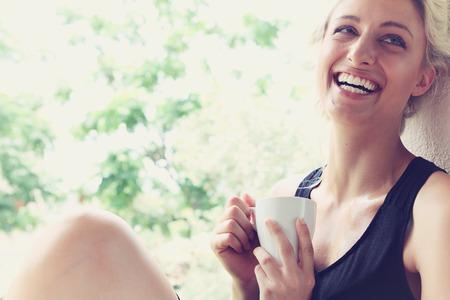 Photo for Pretty woman enjoying her morning coffee on a veranda - Royalty Free Image