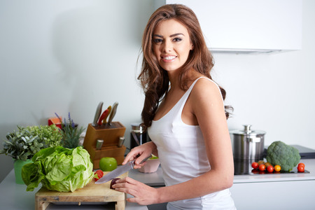 a happy woman cooking a meal in the kitchen.