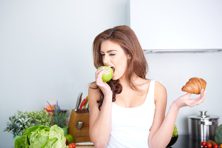 Foto de Diet. Dieting concept. Healthy Food. Beautiful Young Woman choosing between Fruits and Sweets - Imagen libre de derechos