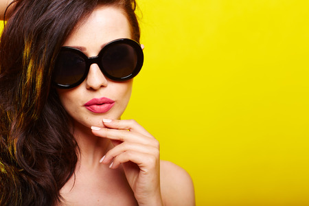 Photo pour caucasian woman wearing sunglasses over yellow background - image libre de droit